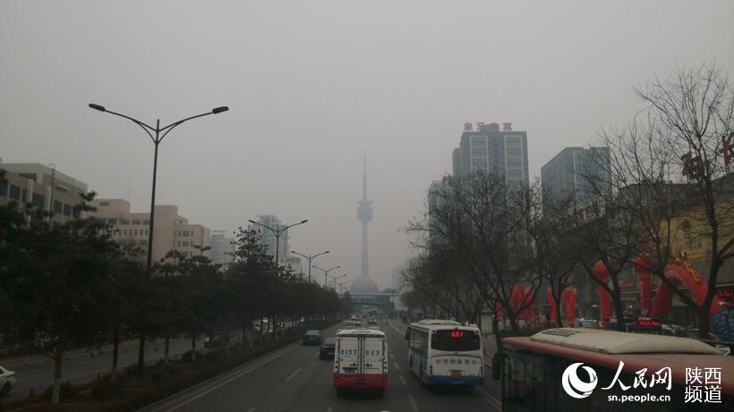 一站路外的电视塔在雾霾中若隐若现.高岗